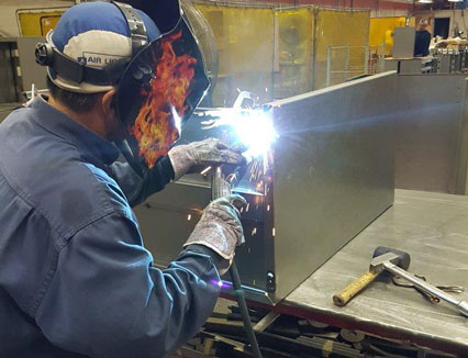 Image of a Dana Precision employee welding a piece of metal.