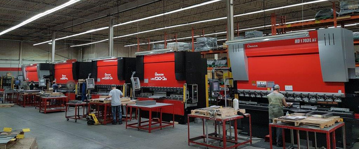 Image of the Dana Precision 41,000 Sq. Ft Manufacturing Facility, with employees working on metal fabrication machines.